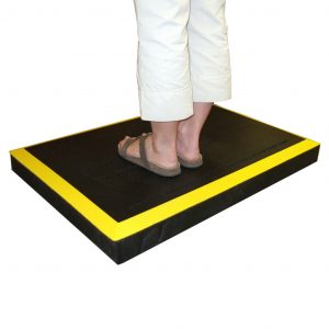 SmartCells ergo riser in black with yellow edges from a diagonal view with a person standing on it